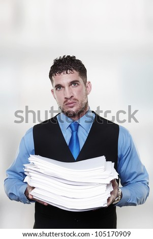 man holding a large pile of paper work in his arms has lot of work to do - stock photo