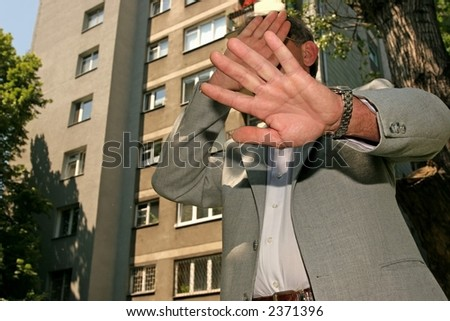 man in a business suit hiding his face from the photographer - stock photo