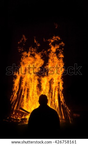 Man in Front of a raging Fire with huge flames of burning timber - stock photo