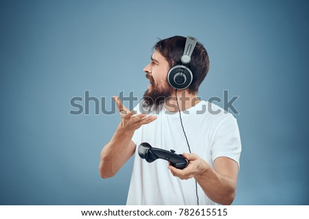 man in headphones with joystick, play in playstation, game console