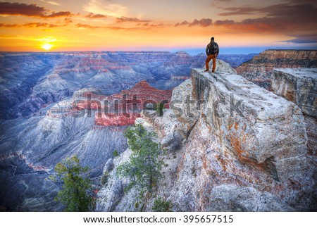 man in the Grand Canyon at sunrise. tourist in America - stock photo