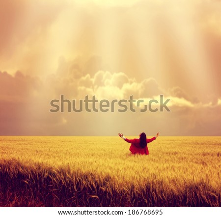 man in wheat field during sunset done with a warm autumn filter - stock photo