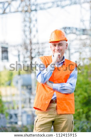 man is the builder on the background of house under construction - stock photo