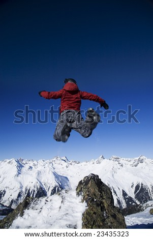 Man jumping over the mountains against blue sky - stock photo