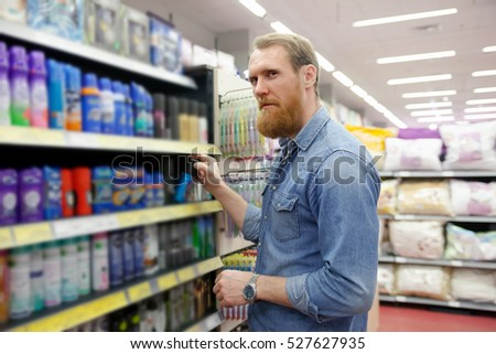 Man near  department with  tools for body care in   supermarket  