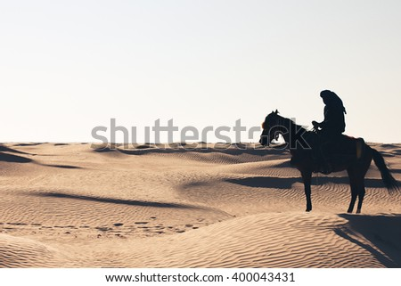 ? man on a horse in the desert. The shadow of a man on a horse in the desert. Arab man on a horse in the desert