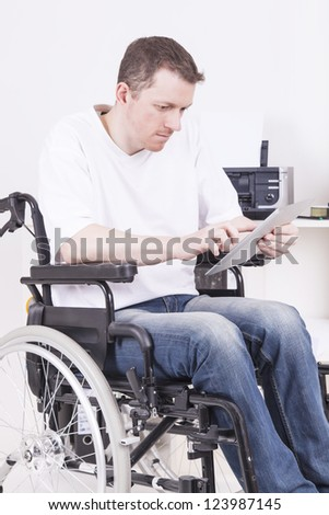 man on wheelchair working in a home office, using a tablet computer - stock photo