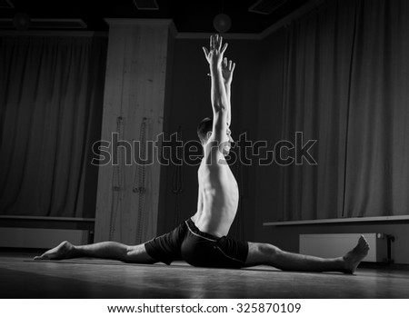 man practicing yoga in sports hall - stock photo