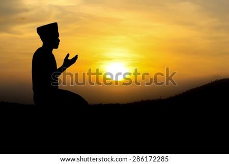 man praying to allah god of Islam on sunset. - stock photo
