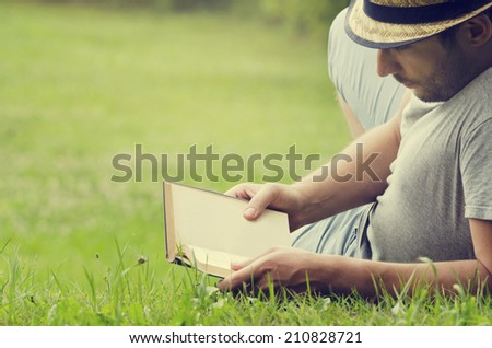 Man reading a book on the grass - stock photo