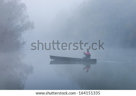 Man rowing in a boat on foggy morning - stock photo