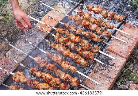 Man's hand turn over kebabs on a grill for better quality of preparation  - stock photo