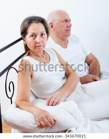 man sitting in bed and quarrelling with his wife.
