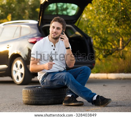 man sitting near car with punctured tire - stock photo