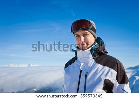 Man standing on a background of snow-capped mountains and looking at the camera. Active man resting in the winter mountains enjoying vacation.