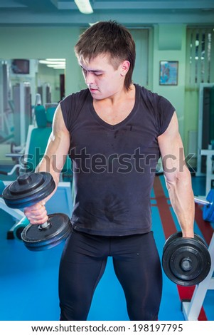 Man training with athletic barbell in gym