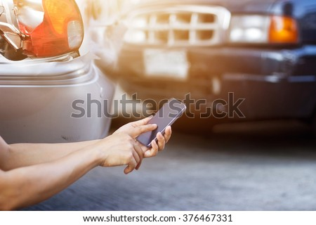 Man using smartphone at roadside after traffic accident - stock photo