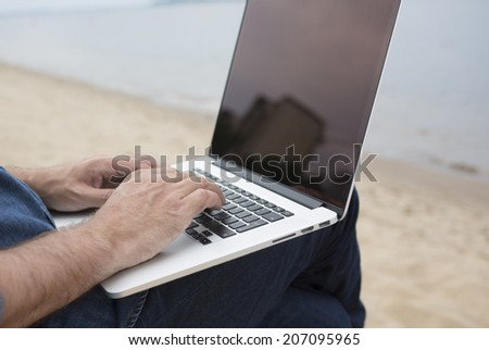 man with laptop on the beach - stock photo