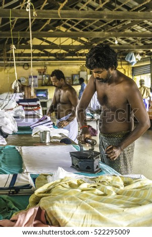 19/10/2016 man working ironing clothes and linens at commercial laundry dhobi khana