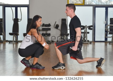 Man working out while female personal  instructor assisting him - stock photo