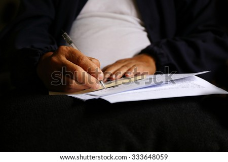 man write pen on document paper ,Close shot of a human hand writing something on the paper on the foreground, think and plan business. - stock photo