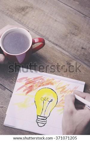 man writing on paper bulb. - stock photo