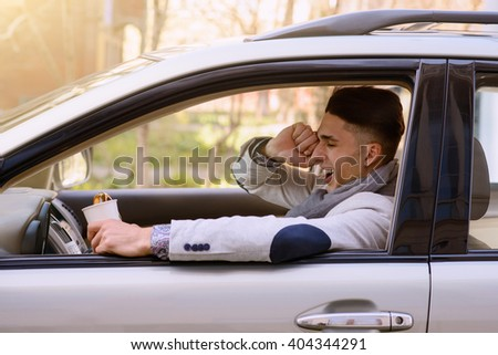 man yawns behind the wheel of a car with a cup of coffee - stock photo