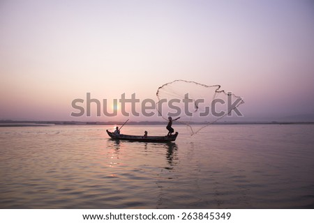 -MANDALAY, MYANMAR - MAR 5: A fisherman catches fish for food in Ayeyarwaddy river on March 5, 2015 in Mandalay, Myanmar. - stock photo