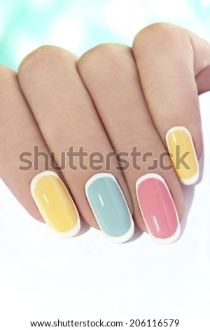 Manicure on an oval shaped nails in pastel colored tones. - stock photo