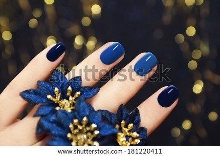 Manicure on women's hands are covered with blue lacquer two tones with flowers. - stock photo