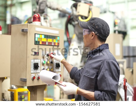 Manufacturing worker operating a robot machine with a control panel  - stock photo