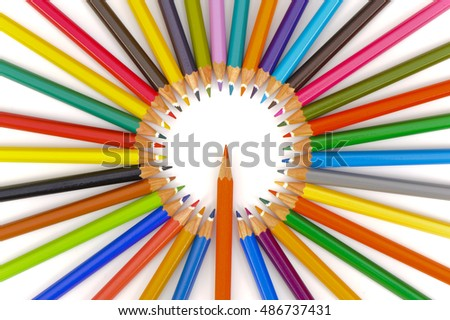 many crayons in circle with red pencil in center as symbol for teamwork