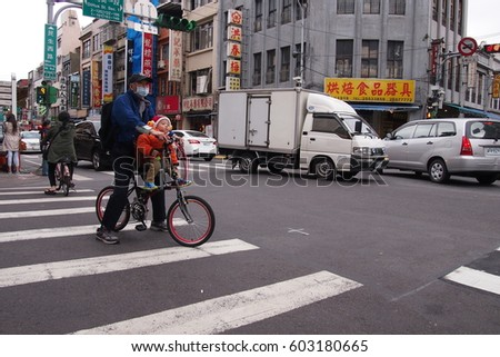 3, March, 2017 - A grandfather giving a ride to his grandchild on a bike in taipei, taiwan