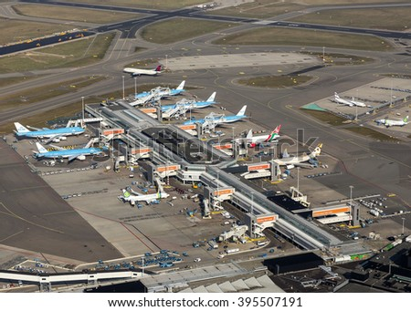 16 March 2016, Amsterdam. Aerial view of 8 jets from KLM, Transavia, Etihad and Kenya Airways at the E-gate at Schiphol Airport, Netherlands. In the back is a Delta Airlines Boeing on the taxiway. - stock photo