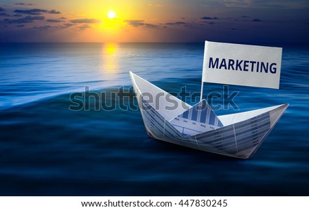 Marketing word with boat made from business paper graph on sea and sun light.For business marketing and financial concept ideas. - stock photo