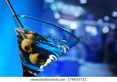 martini with green olives ,focus on a berry - stock photo