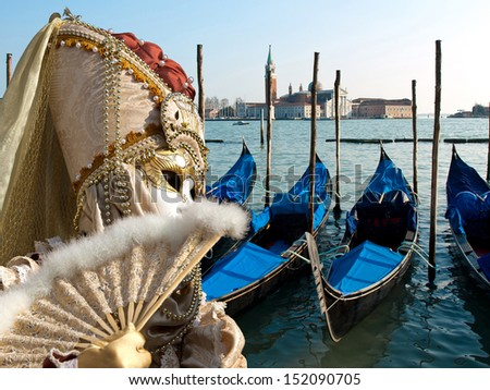 mask and gondola boats waiting for turists in the Venice - stock photo