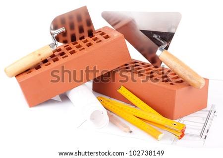 mason tools and house construction plans - stock photo
