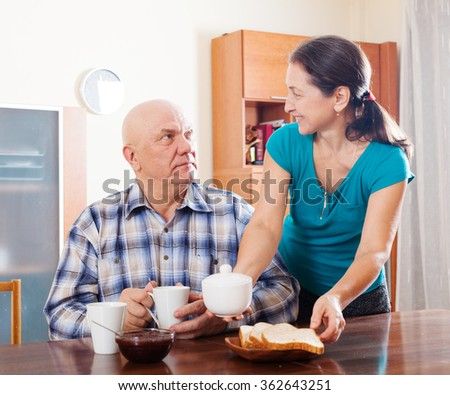 mature couple having breakfast  in morning at home interior - stock photo