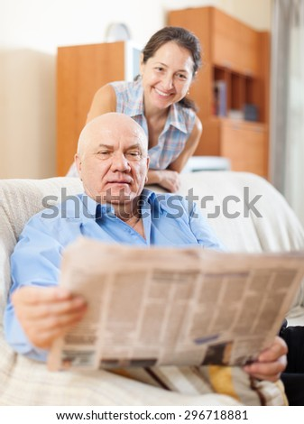 mature couple reading newspaper  together at home - stock photo