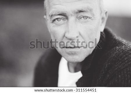 Mature handsome gray-haired man close up looking at the camera and posing - stock photo