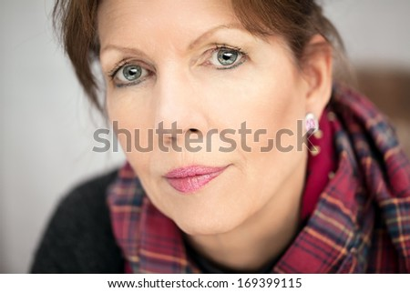 Mature lady looking  seriously at camera - stock photo