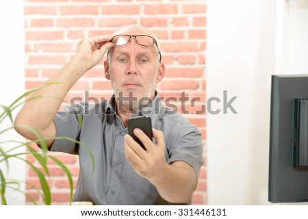 Mature man having trouble seeing cell phone screen because of vision problems - stock photo