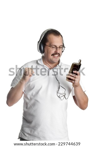 Mature man listening to music on headphones in casual wear. - stock photo