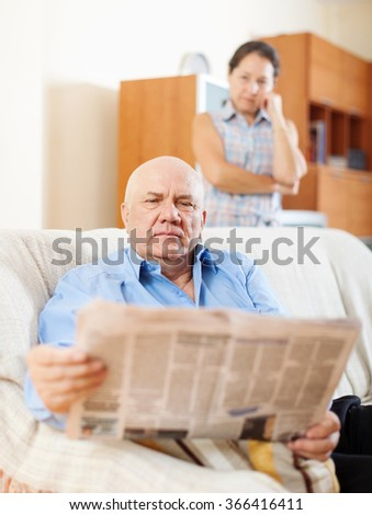 mature man reading newspaper against sad woman in home  - stock photo