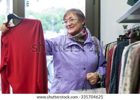 Mature woman choosing     blouse in   clothing store.  - stock photo