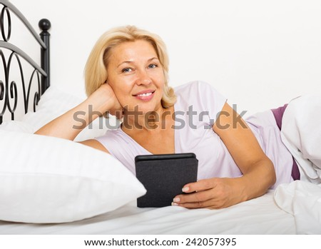 mature woman resting with ereader  on bed - stock photo