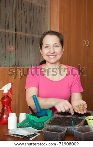Mature woman sows seedlings at her  home