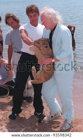 "14MAY98: Actors RICHARD HARRIS (right) & JOHN MICHIE with lion cub on the beach at the Cannes Film Festival to promote their upcoming movie, ""To Walk With Lions.""  The movie is a remake of ""Born Free."" - stock photo"