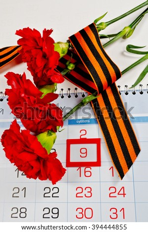 9 May card - three red carnations wrapped with George ribbon on the calendar with 9th May date- holiday that commemorates the victory of Soviet Union in the Great Patriotic War. 9 May concept.  - stock photo